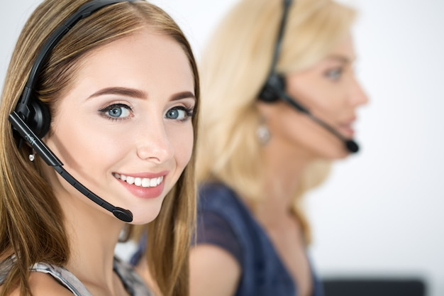 Portrait of call center worker accompanied by her team. smiling customer support operator at work. help and support concept