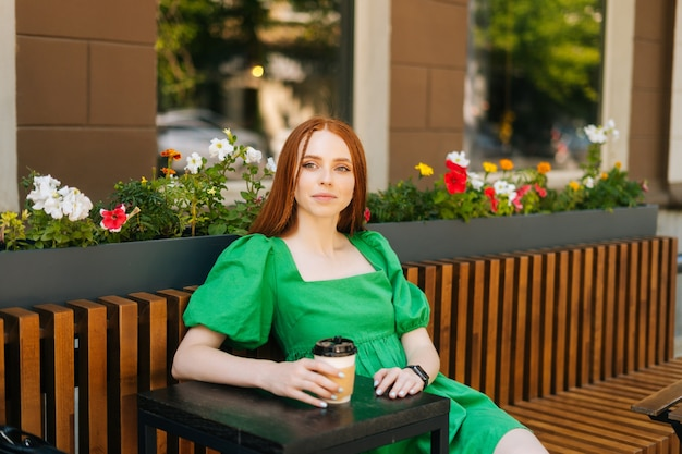 Portrait of calm attractive young woman holding cup with tasty coffee sitting at table in outdoor cafe terrace in summer day. pretty happy redhead lady relaxing vacation on urban street, looking away.