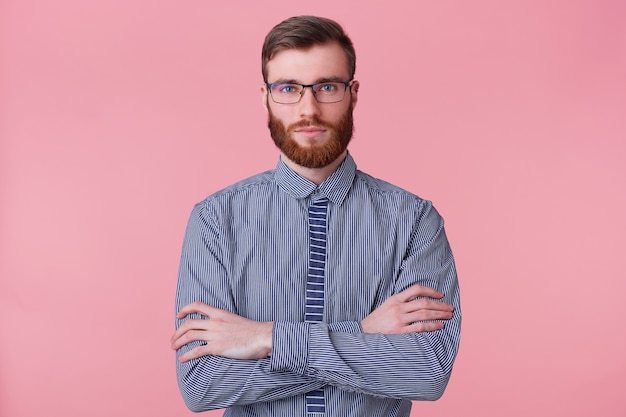 Portrait of a calm bearded young man wears a striped shirt, keeps his arms crossed and looking at the camera isolated on a pink background.
