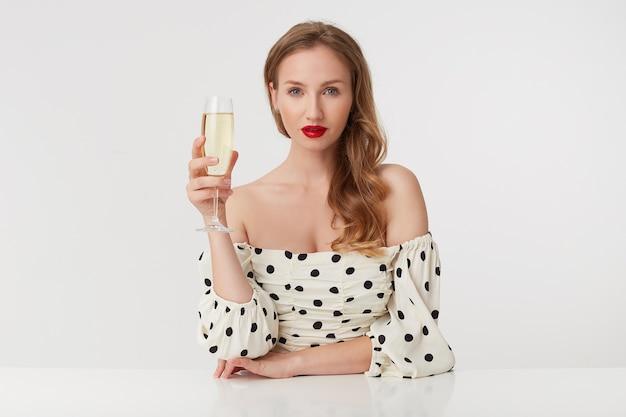 Ritratto di una calma bella giovane bionda dagli occhi azzurri con labbra rosse in un abito a pois. ubicazione al tavolo alzando un bicchiere di champagne, isolato su sfondo bianco.