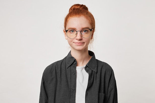 Portrait of calm confident girl with red hair gathered in a bun looks straight into the camera