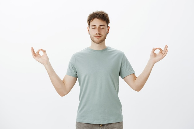 Portrait of calm good-looking caucasian man in t-shirt, smiling and feeling relaxed, standing with spread hands in zen gesture and closed eyes