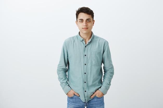 Ritratto di studente universitario maschio di bell'aspetto calmo in camicia casual