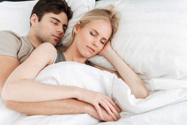 Portrait of calm handsome couple sleeping in bed