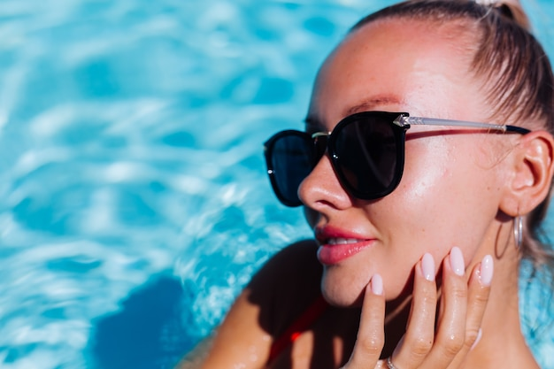Portrait of calm happy woman in sunglasses with tanned skin in blue swimming pool at sunny day