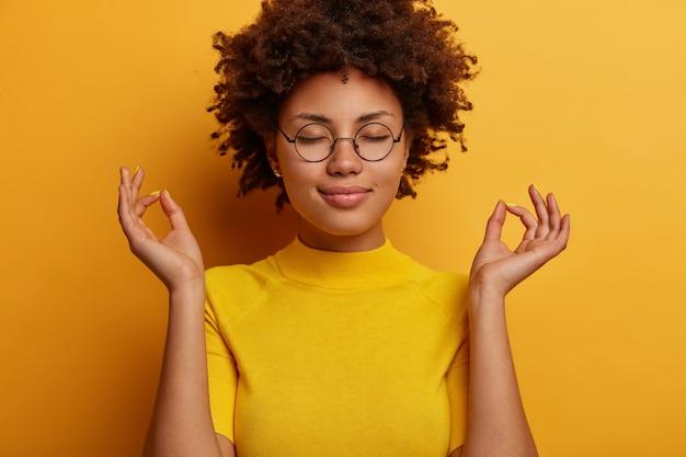 Ritratto di giovane donna in buona salute calma chiude gli occhi e fa meditazione