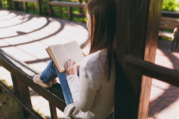 Portrait of calm peaceful young woman wearing light casual clothes relaxing, reading book. female resting in city park in street outdoors on spring nature. lifestyle concept. back view. copy space.