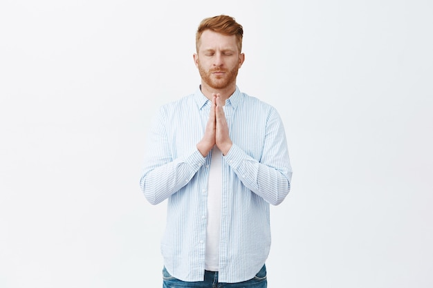 Portrait of calm serious-looking mature redhead european man in shirt, holding hands in pray near chest, closing eyes, praying in asian style near shrine over gray wall