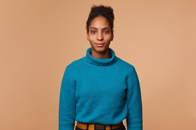 Portrait of calm young african american woman with curly dark hair , wearing a blue sweater, isolated.