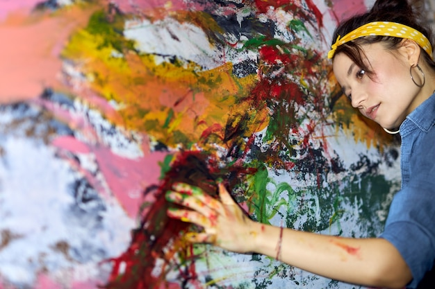 Portrait of calm young woman female painter looking relaxed while applying paint on canvas with