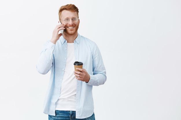Ritratto di modello maschio europeo calmo e freddo spensierato con setole e capelli rossi, che tiene tazza di caffè di carta, che tiene smartphone vicino all'orecchio