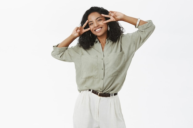 Portrait of carefree charming and upbeat young african american sucessful female in blouse and pants