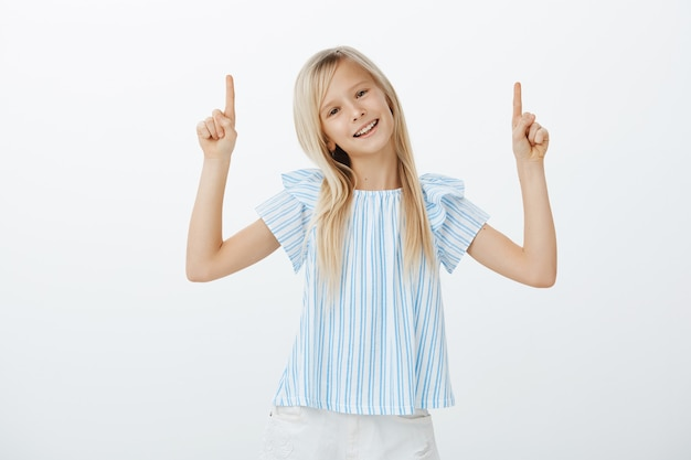 Portrait of carefree confident little child with blond hair in stylish outfit, raising index fingers and pointing upwards, tilting head with cute pleased smile, showing something awesome to friends