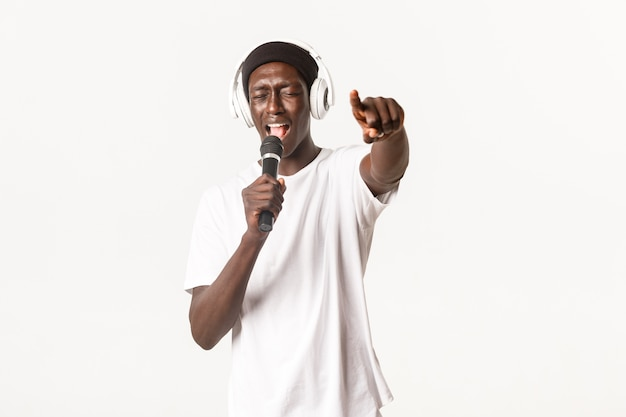 Portrait of carefree and cool african-american young man, performing in karaoke, singing into microphone while wearing headphones