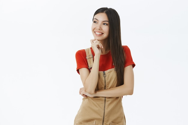 Portrait of carefree delighted and stylish female entrepreneur with long dark hair dreaming or thinking