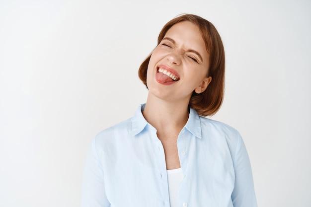 Ritratto di una studentessa spensierata che sorride con gli occhi chiusi, che mostra la lingua e che ha la lingua, in piedi giocoso sul muro bianco