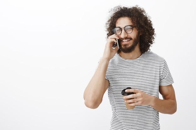 Ritratto di spensierato bell'aspetto barbuto con gli occhiali, parlando sullo smartphone e guardando da parte con un sorriso gioioso, tenendo la tazza di caffè o tè