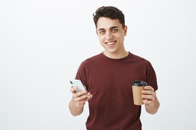 Ritratto del modello maschio bello spensierato in maglietta rossa con smartphone e tazza di caffè