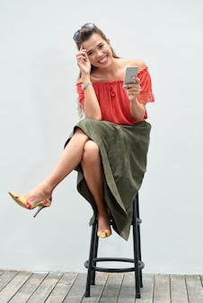 Portrait of carefree lady seated on bar stool with a smartphone