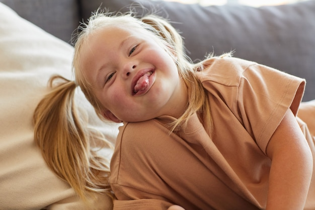 Portrait of carefree little girl with down syndrome sticking tongue out while grimacing for camera