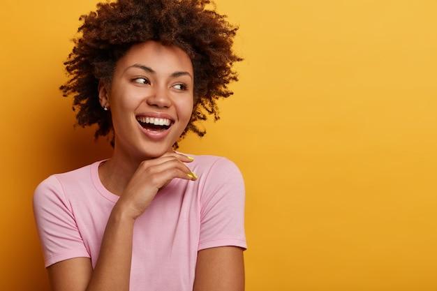 Ritratto di spensierata giovane donna afroamericana positiva ha un sorriso raggiante, tocca delicatamente il mento e distoglie lo sguardo, felice di notare qualcosa di attraente, indossa abiti casual, ha una bellezza naturale