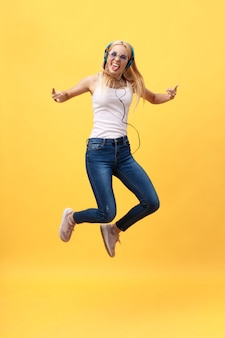Portrait of carefree woman in jean jumping while listening music.
