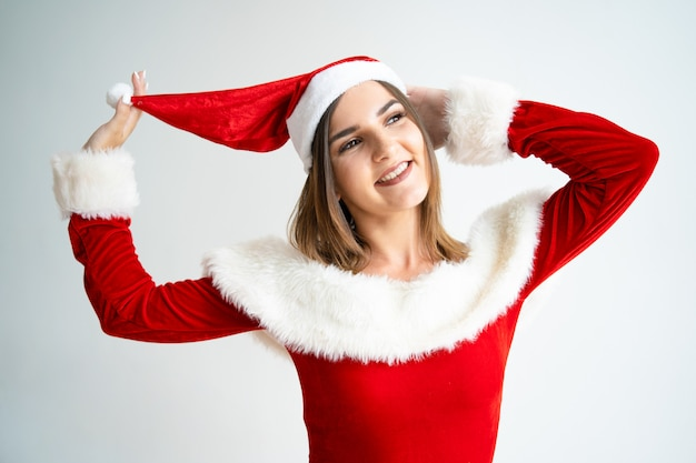 Portrait of carefree woman in santa claus dress playing with hat