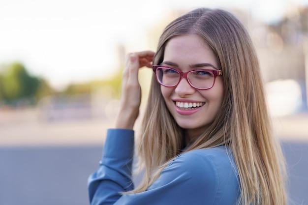 Ritratto di spensierata giovane donna sorridente con strada urbana. allegra ragazza caucasica indossando occhiali da vista in città.