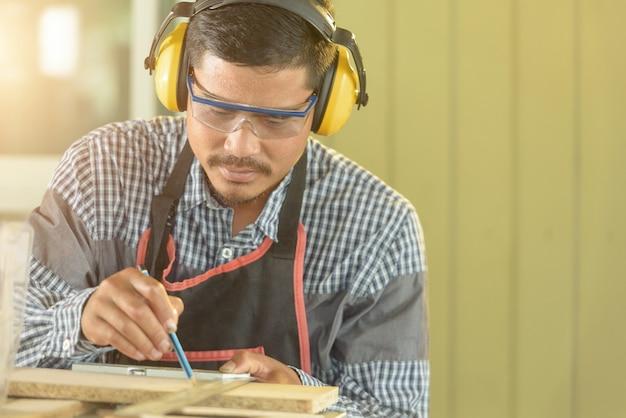 肖像画の大工の男幸せな魅力的な勤勉な探してワークショップで木材を選択します。大工は大工店の木製のテーブルの機器を操作します。