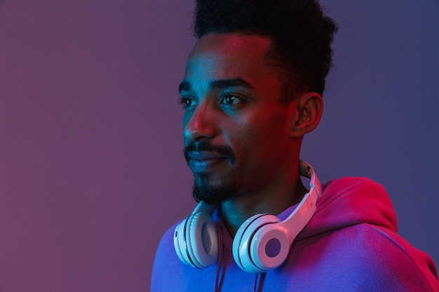 Portrait of casual african american man in colorful hoodie posing with headphones isolated over violet wall