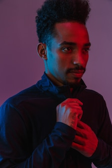 Portrait of casual african american man in sportswear posing at  isolated over violet wall