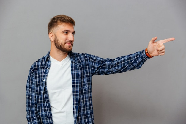Portrait of a casual bearded man pointing finger away isolated on a gray wall