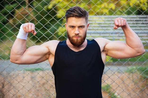 Portrait of a casual bearded man showing biceps and looking at front outdoors