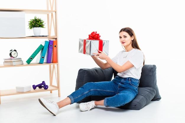 Ritratto di una ragazza casuale che si siede su un pavimento con la pila di contenitori di regalo e distogliere lo sguardo isolato sopra la parete bianca