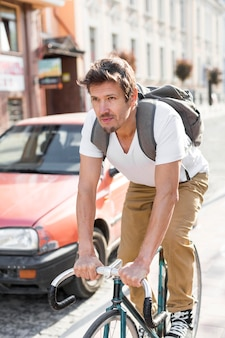 Portrait of casual male riding bike in the city