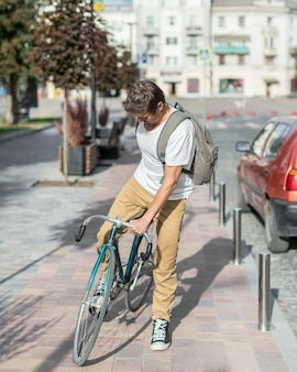 Portrait of casual male riding bike outdoors