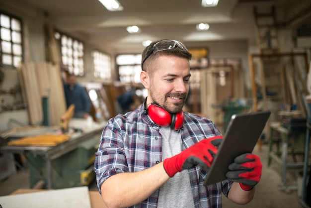 Portrait of casual middle aged worker carpenter with tablet in carpentry workshop