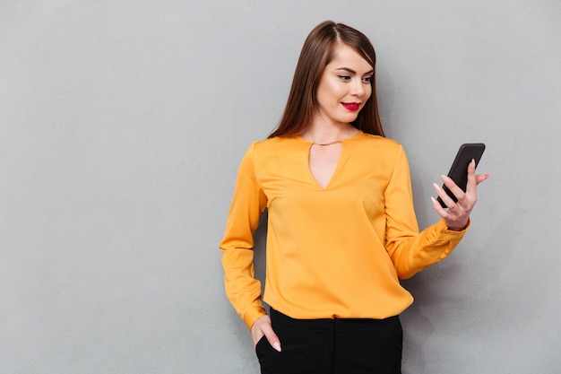 Portrait of a casual woman looking at mobile phone screen