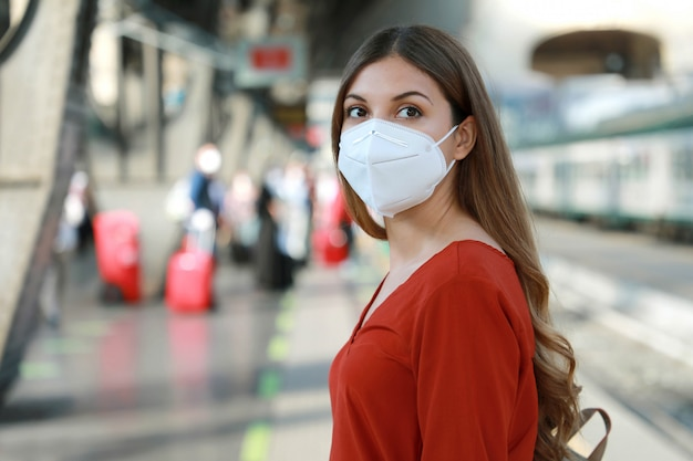 Portrait of casual woman waiting train with kn95 ffp2 protective mask at train station