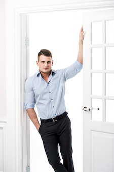 Portrait casual young man leaning against the frame of an open door on light background smiling and looking to camera with hand in his pocket