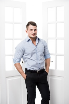 Portrait casual young man leaning against the frame of an open door on light background smiling and looking to camera with hand in his pockets