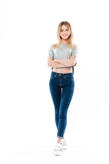 Portrait of a casual young young woman standing with hands folded