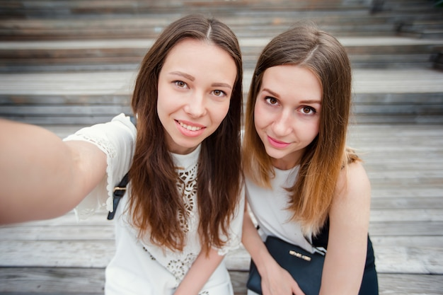Portrait of caucasian beautiful girls making selfie outdoors. young tourist friends traveling on holidays smiling happy.