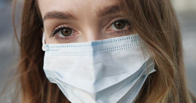 Portrait of caucasian beautiful woman in medical mask. close up of pretty girl wearing protection from virus outdoor in city.