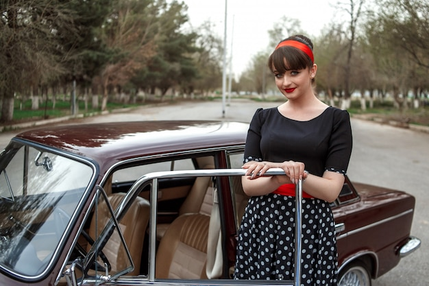 Portrait of caucasian beautiful young girl in black vintage dress who sits in a retro car