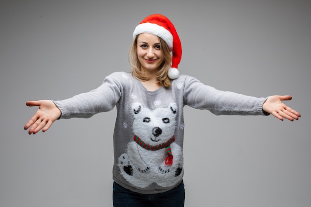 Portrait of caucasian blonde woman in red santa hat and winter sweater with polar bear outstretching her arms
