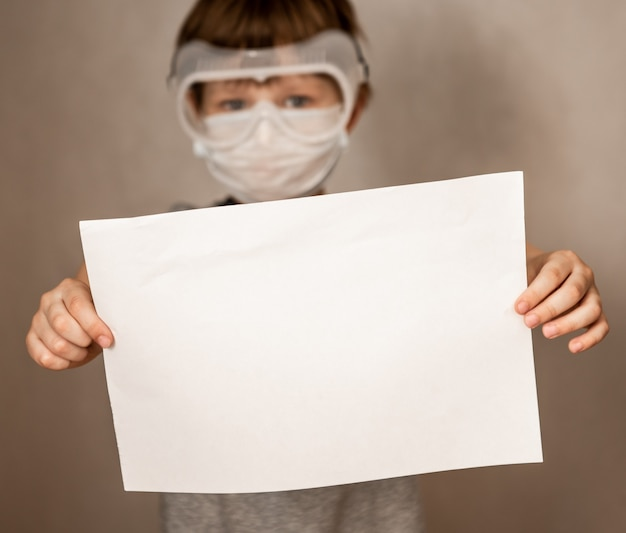 Portrait of caucasian boy in a protective mask respirator holds a blank sheet of paper on gray background. protection against coronavirus. mock up, copy space, advertisement