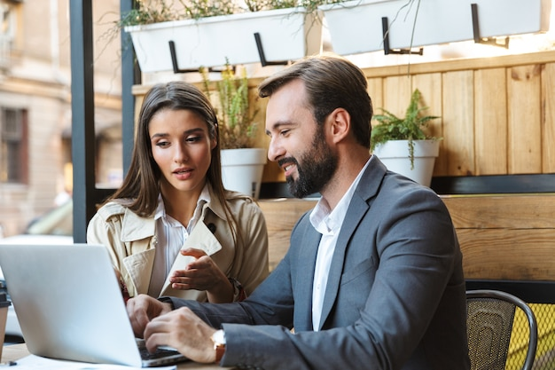Portrait of caucasian business couple man and woman in formal wear having conversation and working on laptop together while sitting in cafe outdoors