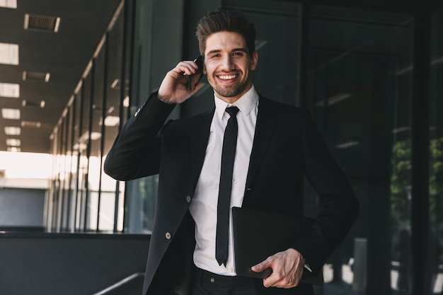 Portrait of caucasian businessman dressed in formal suit walking outside glass building, and talking on mobile phone