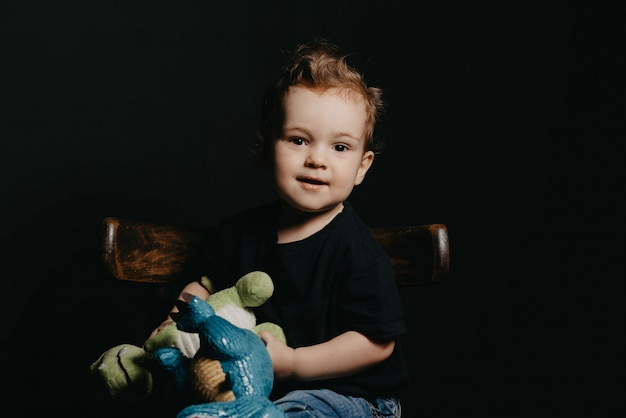 Portrait of a caucasian child boy playing with dinosaur toys